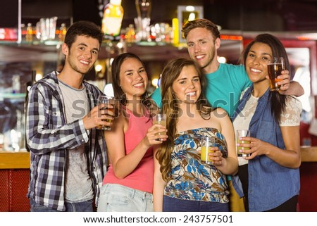 Smiling friends drinking beer and mixed drink in a bar - stock photo