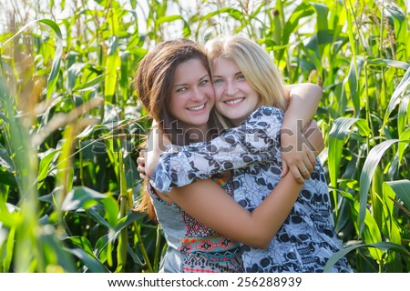 Smiling friends embracing at green corn field background - stock photo