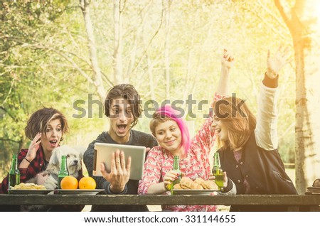 Smiling friends in the park, with food on the table, watching sport game on a tablet pc  on a sunny day with their dog - Caucasian people - people, nature, animal, technology and lifestyle concept - stock photo