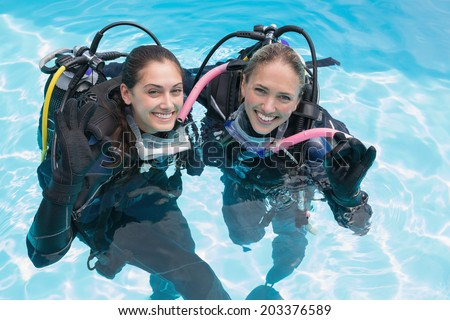 Smiling friends on scuba training in swimming pool making ok sign on a sunny day - stock photo
