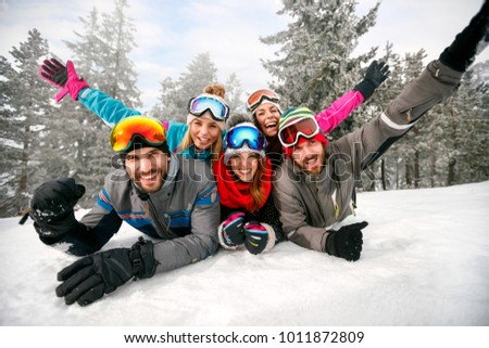 smiling friends on winter holidays â?? Happy skiers lying on snow and having fun