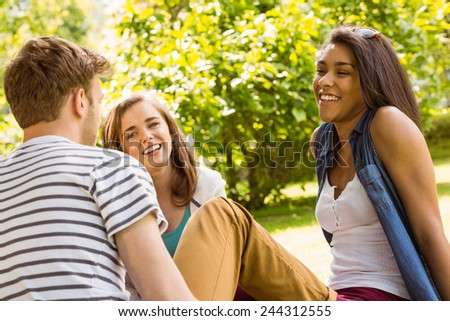 Smiling friends student sitting and talking in park at school - stock photo