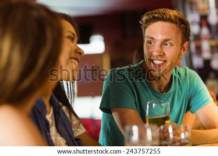 Smiling friends talking and drinking beer in a bar - stock photo