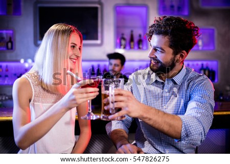 Smiling friends toasting cocktail and beer glass at bar counter in bar