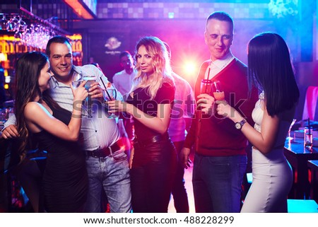 Smiling friends toasting with beer and cocktails in a nightclub