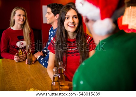 Smiling friends with christmas accessory in the bar
