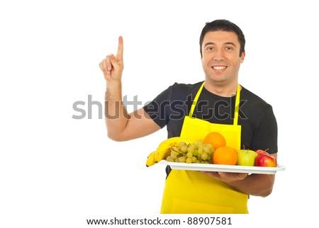 Smiling fruiterer holding fruits and pointing upwards isolated on white background - stock photo