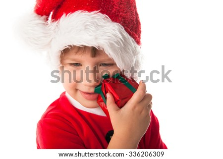Smiling funny child girl in Santa red hat holding Christmas gift in hands. Christmas concept. play with gift