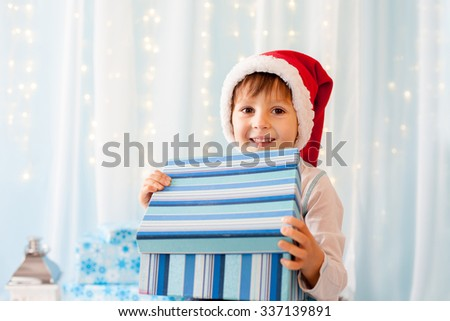 Smiling funny child in Santa red hat holding Christmas gift in hand - stock photo