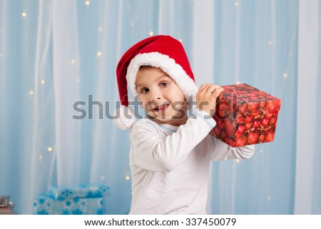 Smiling funny child in Santa red hat holding Christmas gift in hand, Christmas concept. - stock photo