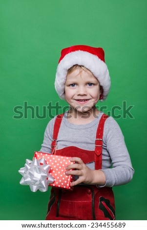Smiling funny child in Santa red hat. Holding Christmas gift in hand. Christmas concept. Studio portrait over green background - stock photo