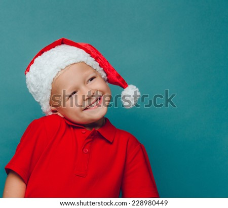 Smiling funny child (kid, girl) in Santa red hat. Christmas concept.
