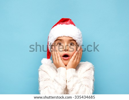 Smiling funny child (kid, girl) in Santa red hat.. Christmas concept. Shooting on blue background - stock photo