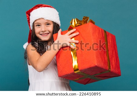 Smiling funny child (kid, girl) in Santa red hat holding Christmas gift in hand. Christmas concept.