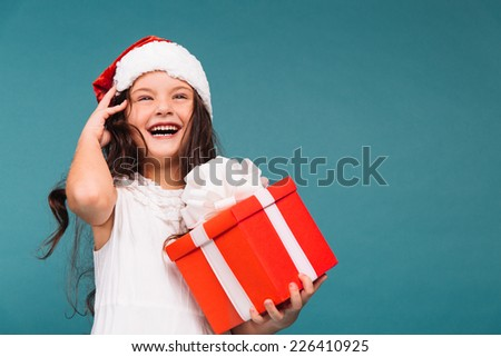 Smiling funny child (kid, girl) in Santa red hat holding Christmas gift in hand. Christmas concept. - stock photo