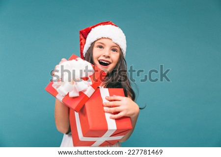 Smiling funny child (kid, girl) in Santa red hat. Holding Christmas gift in hand. Christmas concept. Shooting on blue background