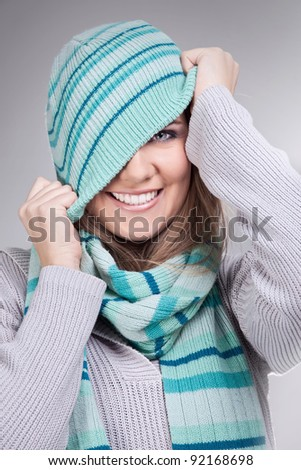 smiling funny girl pulling her winter hat