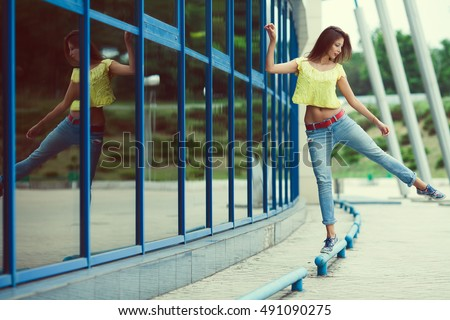 Smiling funny hipster girl in blue jeans dancing and balancing in the summer city. Modern youth lifestyle concept. Outdoor shot