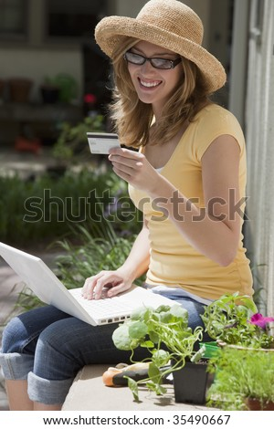 Smiling gardener shopping on-line with credit card and laptop outside - stock photo