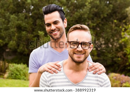 Smiling gay couple hugging in garden - stock photo