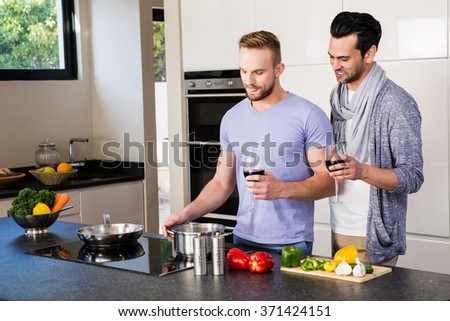 smiling gay couple preparing food in the kitchen - stock photo