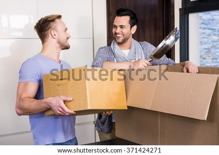 Smiling gay couple unpacking cardboard in the kitchen - stock photo