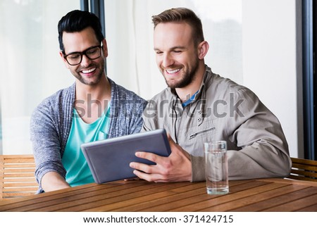 Smiling gay couple using tablet outdoors - stock photo