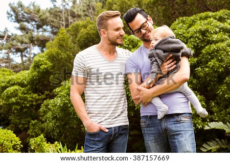 Smiling gay couple with child in garden - stock photo