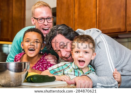 Smiling gay parents with their children in the kitchen - stock photo