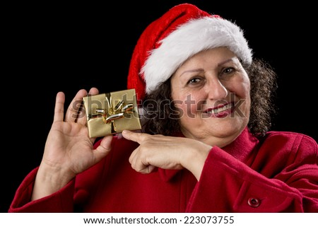 Smiling gentle woman with red coat and Santa Claus cap isolated on black background. Pointing her left index finger at a wrapped golden Christmas present held up by her right hand. Gift-giving theme.  - stock photo