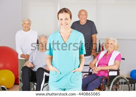 Smiling geriatric nurse standing in front of a happy group of senior people - stock photo