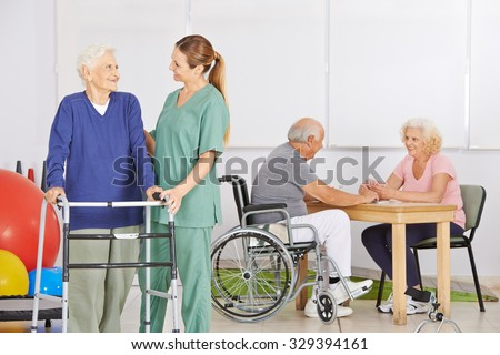 Smiling geriatric nurse with group of senior people in a nursing home - stock photo