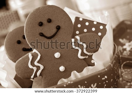 Smiling gingerbread man nestled in holiday dish with gift-wrapped surprise.  Baking supplies in soft focus in background. Sepia toned for a nostalgic feel. - stock photo