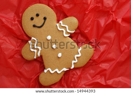 Smiling gingerbread man on crumpled, red tissue paper.