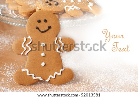 Smiling gingerbread man with additional cookies and dusting of confectioners sugar in background.  Macro with shallow dof and copy space. - stock photo