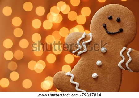 Smiling gingerbread man with lights in background.  Macro with shallow dof. - stock photo