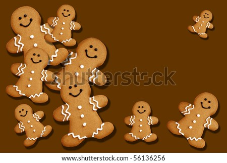 Smiling gingerbread men on brown background with copy space. - stock photo