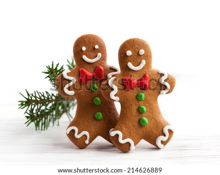 Smiling gingerbread men on white wooden background - stock photo