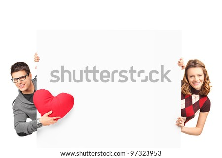 Smiling girl and boy with heart shaped pillow posing behind a white panel isolated on white background - stock photo