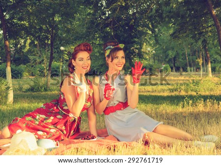 Smiling girl at a picnic waving retro - stock photo