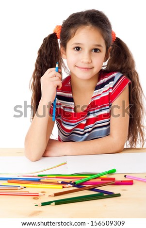 Smiling girl at the table draw the rainbow, isolated on white
