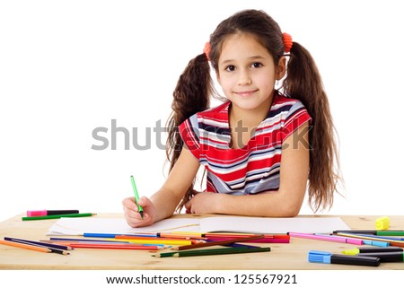 Smiling girl at the table drawing in the notebook, isolated on white - stock photo