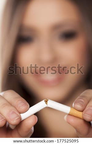 smiling girl breaks a cigarette with a focus on the foreground