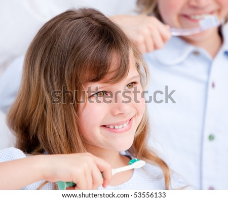 Smiling girl brushing her teeth against a white background - stock photo