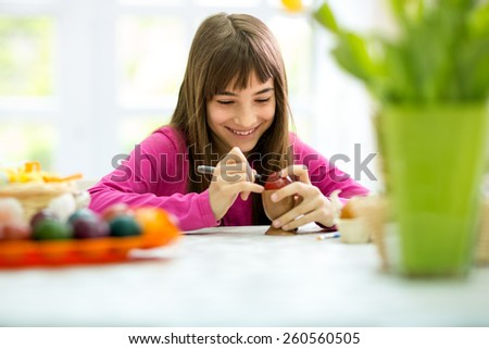 smiling girl coloring Easter eggs - stock photo