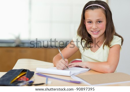 Smiling girl doing her homework in the kitchen