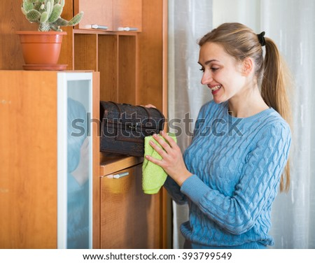 Smiling girl doing regular clean-up and dusting at home