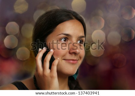 Smiling girl during phone call on bokeh background - stock photo