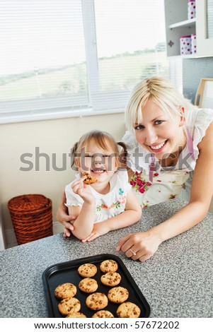Smiling girl eating cookie in kitchen - stock photo