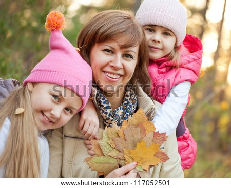Smiling girl embracing her mother with sister close by
